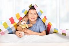 Skämtsam unge som rymmer en nallebjörn under en filt Royaltyfri Bild