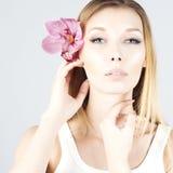 Skönhetblondin med rosa färgblomman i hår Frikänd och ny hud Härlig le flicka Royaltyfria Bilder