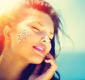 Skönhetflicka som applicerar Sun Tan Cream Fotografering för Bildbyråer