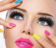 Skönhetflickan med färgrikt spikar polermedel Arkivfoton