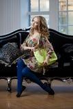 Skönhetkvinna i lyxig sofa med handväskan Arkivbilder