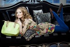 Skönhetkvinna i lyxig sofa med handväskan Royaltyfri Bild