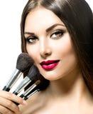 Skönhetkvinna med makeupborstar Arkivbilder