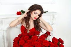 Skönhetmodellflicka med makeup, långt hår och härliga röda rosor Fotografering för Bildbyråer