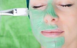 Skönhetsalong. Kosmetolog som applicerar den ansikts- maskeringen på kvinnaframsidan. Arkivbild