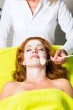 Skönhetsmedel och skönhet - applicera den ansikts- maskeringen Arkivfoton