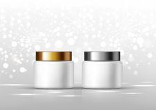 Skönhetsmedelflaskor för kräm Den vit kruset och guld, försilvrar det glansiga locket på den gråa bakgrunden för annonser Arkivbilder