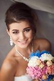 Skönhetstående av den hållande buketten för ung brud Perfekt makeup a Royaltyfri Foto