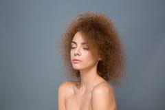 Skönhetstående av den unga naturliga kvinnan med den omfångsrika lockiga frisyren Royaltyfri Bild