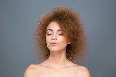 Skönhetståenden av den lockiga avkopplade unga kvinnan med ögon stängde sig Arkivbild