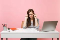 Skołowana zmęczona kobieta ma problemowego mienia ołówkową pobliską twarz siedzi, pracuje przy białym biurkiem z współczesnym kom obraz royalty free