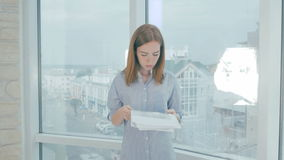 Skołowana kobieta stresuje się out nad papierami, rzuca one w powietrze w nowożytnym biurze zdjęcie wideo
