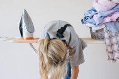 Skołowana kobieta za prasowania biurkiem zdjęcie royalty free