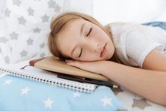 Skołowana młoda dama śpi nad notatnikami z domowymi zadaniami fotografia royalty free
