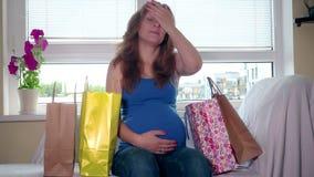 Skołowany kobieta w ciąży z kolorowymi torba na zakupy siedzi i relaksuje na kanapie zdjęcie wideo