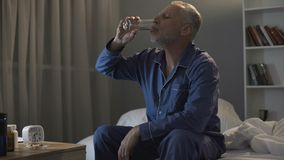 Skołowany mężczyzna w jego 50s obsiadaniu w łóżku i brać przy nocą antidepressants zdjęcie royalty free