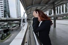 Skołowany młody Azjatycki bizneswoman z ręką na twarzy uczuciu męczącym przy miasta tłem i burnout z jego pracą Sfrustowany s obrazy royalty free