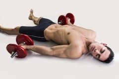 Skołowany młody męski bodybuilder odpoczywa na podłoga Fotografia Stock