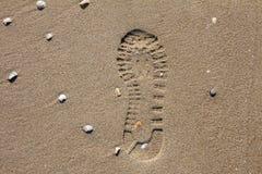 Sko avtrycken i sanden av en strand Royaltyfria Bilder