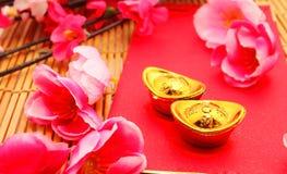 Sko-formad guldtacka (Yuan Bao) och Plum Flowers med det röda paketet Fotografering för Bildbyråer