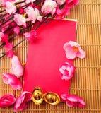 Sko-formad guldtacka (Yuan Bao) och Plum Flowers med det röda paketet Arkivbilder