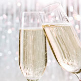 Skoal. Two elegant flutes of sparkling white champagne with lots of bubbles on festive background, celebration concept Royalty Free Stock Photo
