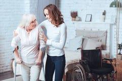 Skoczna młoda kobieta pomaga obezwładniającej starzejącej się damy w domu zdjęcia royalty free