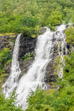 Skoczny siklawy spływanie zestrzela skały w lesie obramiającym drzewami Zdjęcia Stock