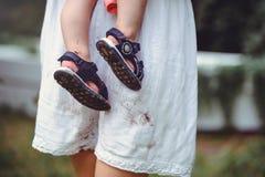 Skodd fot av ett barn i armarna av en moder, en vit klänning som befläckas med skor som lyfter barn och älskar dem Royaltyfri Fotografi