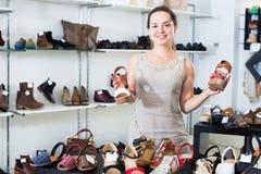 Skodon shoppar den vänliga flickan som poserar med olika skor fotografering för bildbyråer