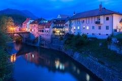 Skofja Loka, Slovenien: Nattsikt av de gamla historiska husen och stenbron Royaltyfria Foton