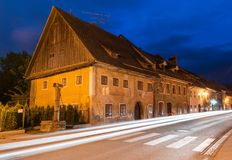 Skofja Loka, Slovenien: Smal gata med billjusslingor Royaltyfri Foto