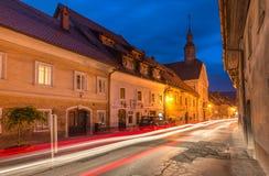 Skofja Loka, Slovenien: Smal gata med billjustraila Royaltyfri Foto