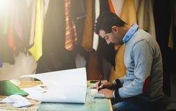 Skoformgivare som arbetar med pappers- modeller för läderklipp fotografering för bildbyråer