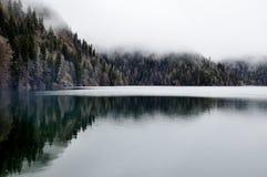 Skog lakereflexion med dimma i Rica, nationalpark Abkhazia arkivbild