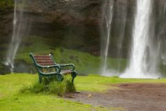 Skogafalls waterfall near against the backdrop of benches in Iceland. The concept of calm. Relaxation stock images