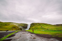 Skogafoss瀑布巨大看法在冰岛和风景周围的 游人看水巨大的流程  库存图片