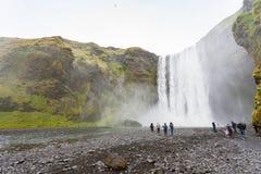Skogafoss瀑布底部的人们  免版税图库摄影