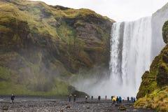 Skogafoss瀑布底部的游人  免版税图库摄影