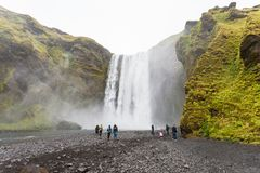 Skogafoss瀑布底部的访客  免版税库存图片