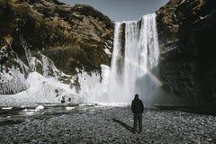 Skogafoss瀑布秀丽与彩虹的冰岛找出的人admirnig 免版税图库摄影