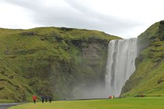 Skogafoss. Famous Skogafoss waterfall with tourists walking towards it on Iceland Stock Images