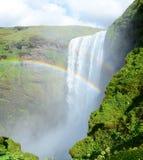 Skogafoss vattenfall med den dubbla regnbågen Arkivfoto
