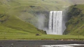 Skogafoss vattenfall och traktor som plogar fältet. Island. Södra ar arkivfoton