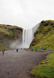 Skogafoss vattenfall och turister i sommaren, Island Royaltyfri Fotografi