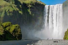 Skogafoss waterfall. Blurred tourists under Skogafoss waterfall on the South of Iceland near the town Skogar Stock Photos