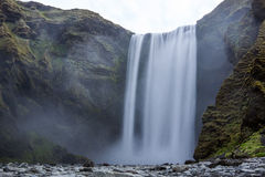 Skogafoss waterfall in Iceland. Long exposure to smooth the water. Rocks in foreground Stock Image