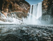 Skogafoss waterfall in Iceland with rainbow on a sunny day with blue sky. stock image