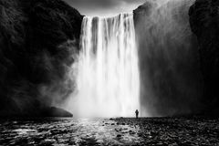 Skogafoss waterfall with a lonely man Royalty Free Stock Photos