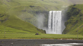 Skogafoss waterfall and tractor plowing field. Iceland. South ar Stock Photos